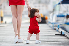 Mother teaches little daughter to walk alone Stock Images