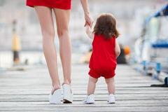 Mother teaches little daughter to walk alone Stock Photo