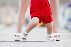 Mother teaches little daughter to walk alone Stock Photos