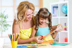 Mother teaches preschooler kid to do craft items Stock Photography