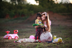 Mother teaches reading book to daughter Royalty Free Stock Photography