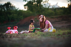 Mother teaches reading book to daughter Stock Image