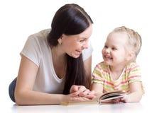 Mother teaches reading book to kid Stock Photos