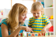 Mother teaches son child to read letters and words playing with cubes Royalty Free Stock Photography
