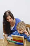 Mother teaches son. Mother teaches her son how to count using an abacus stock photography