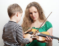 Mother teaches son play violin Stock Photos