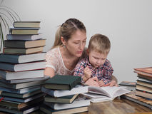 Mother teaches son to read among the stacks of books royalty free stock images