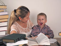 Mother teaches son to read among the stacks of books stock photo