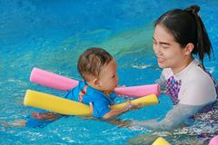Mother teaching baby boy in swimming pool with noodle foam.  royalty free stock photos