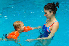 Mother teaching baby boy to swim Stock Photography