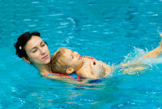 Mother teaching baby boy to swim Stock Images