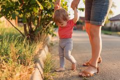 Mother teaching baby daughter first steps outside in the sunset stock photo