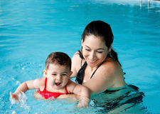 Mother teaching baby swimming. Beautiful mother teaching cute baby girl how to swim in a swimming pool. Child having fun in water with mom stock photo