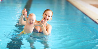 Mother teaching baby swimming pool. Healthy family mother teaching baby swimming pool stock photos