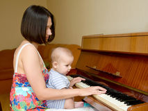 Mother teaching baby to play the piano. Stock Images