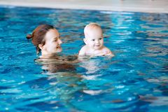 Smiling charming baby in swimming pool. Mother teaching baby to swim. Portrait of a charming 11 months child in the classroom in a swimming pool. Healthy Family Stock Photography