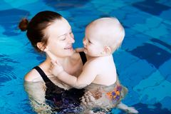 Smiling charming baby in swimming pool. Mother teaching baby to swim. Portrait of a charming 11 months child in the classroom in a swimming pool. Healthy Family Royalty Free Stock Photography