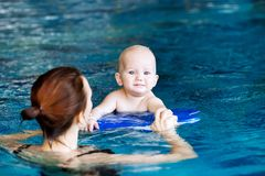 Smiling charming baby in swimming pool. Mother teaching baby to swim. Portrait of a charming 11 months child in the classroom in a swimming pool. Healthy Family Stock Photo