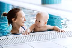 Smiling charming baby in swimming pool. Mother teaching baby to swim. Portrait of a charming 11 months child in the classroom in a swimming pool. Healthy Family Royalty Free Stock Image