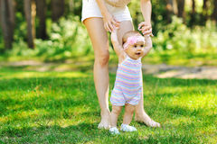 Mother teaching baby to walk in the park stock photo
