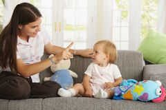Mother teaching babygirl. Sitting on sofa at home, smiling Stock Photography