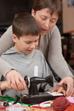 Mother teaching child boy sew, job training, handmade and handicraft concept Royalty Free Stock Photo