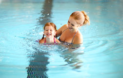 Mother teaching child daughter swimming pool. Healthy family mother teaching child daughter swimming pool Royalty Free Stock Images