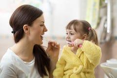 Mother teaching daughter child teeth brushing in bathroom Royalty Free Stock Image