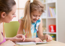 Mother teaching child daughter to read Royalty Free Stock Photography