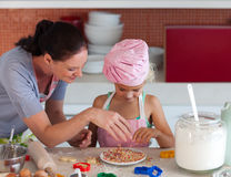 Mother teaching Child how to cook. Young mother in kitchen teaching child how to cook Stock Images