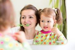 Mother teaching child teeth brushing Stock Photos