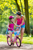 Mother teaching child to ride a bike stock image