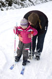 Mother teaching child to ski. Obese mother teaching her daughter how to go cross country skiing Stock Images