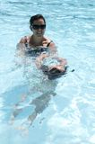 Mother teaching child to swim Stock Photo