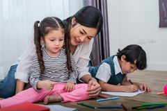 Mother teaching children in drawing class. Daughter and son pain. Ting with colorful crayon color in home. Teacher training students in art classroom. Education stock image