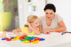 Mother teaching daughter. Mother teaching little daughter drawing at home stock photo