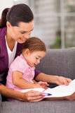 Mother teaching daughter. Mother teaching little daughter drawing at home stock image