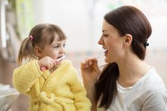 Mother teaching daughter child teeth brushing in bathroom Stock Photography