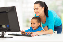 Mother teaching daughter computer. Happy young mother teaching daughter computer at home Stock Images