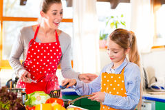 Mother teaching daughter cooking at home stock photos