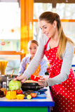 Mother teaching daughter cooking at home Royalty Free Stock Photo