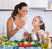 Mother teaching daughter how to cook soup indoors Royalty Free Stock Photography