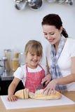 Mother teaching daughter how to cut bread Royalty Free Stock Photography