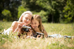 Mother teaching daughter how to take pictures on camera. Stock Photos