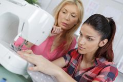 Mother teaching daughter how to use sewing machine. Mother teaching daughter how to use a sewing machine Stock Image