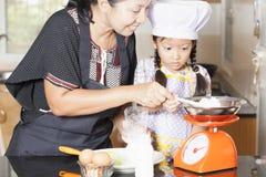 Mother teaching daughter making pancake. In kitchen stock photography
