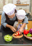 Mother teaching daughter making salad. In kitchen Royalty Free Stock Image