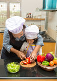 Mother teaching daughter making salad. In kitchen Stock Photos