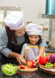 Mother teaching daughter making salad. In kitchen Royalty Free Stock Photography