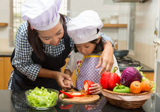 Mother teaching daughter making salad. In kitchen Royalty Free Stock Photo